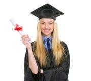 Donna felice in abito di graduazione che mostra diploma Immagini Stock Libere da Diritti