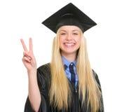Donna felice in abito di graduazione che mostra vittoria Fotografia Stock Libera da Diritti