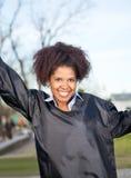 Donna felice in abito di graduazione sulla città universitaria Immagini Stock