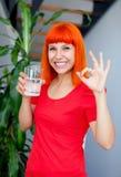 Donna felice in acqua potabile rossa Fotografia Stock