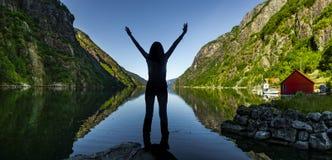 Donna felice ad un fiordo in Norvegia immagine stock libera da diritti