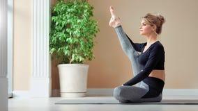 Donna felice adorabile che gode dell'allenamento che mostra allungamento perfetto all'interno dello studio di yoga video d archivio