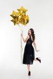 Donna felice allegra attraente che guarda indietro e che tiene i palloni dorati Fotografia Stock