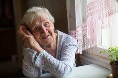 Donna felice anziana che si siede nella sua casa Fotografia Stock