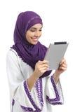 Donna felice araba che legge un lettore della compressa Fotografia Stock