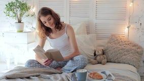 Donna felice attraente che legge un libro che si siede sul letto alla prima colazione stock footage