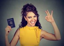 Donna felice attraente con il passaporto di U.S.A. che dà segno giusto Fotografie Stock