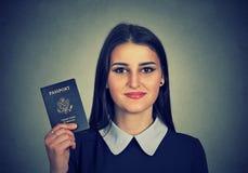 Donna felice attraente del ritratto giovane con il passaporto di U.S.A. Immagini Stock Libere da Diritti