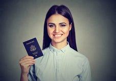 Donna felice attraente del ritratto giovane con il passaporto di U.S.A. sul fondo grigio della parete Espressione umana positiva  Immagine Stock Libera da Diritti