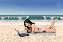 Donna felice in bikini con il computer portatile alla spiaggia Fotografia Stock