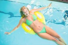 Donna felice in bikini verde che si rilassa sul tubo gonfiabile nella piscina fotografia stock libera da diritti