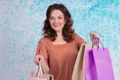 Donna felice in blusa arancio che tiene il sacco di carta di acquisto variopinto Fotografia Stock Libera da Diritti