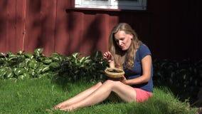 Donna felice in breve che si siedono vicino alla casa di legno rurale che mangia la bacca nera e sorriso della mora 4K archivi video