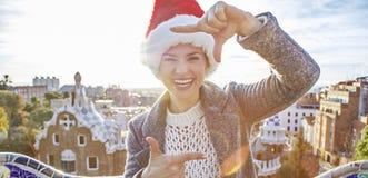 Donna felice in cappello di Santa al parco di Guell con l'inquadramento delle mani Immagini Stock Libere da Diritti