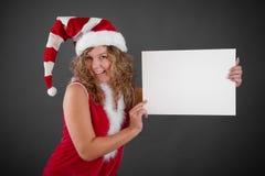Donna felice in cappello di Santa che tiene segno in bianco Fotografia Stock Libera da Diritti