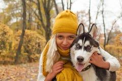 Donna felice che abbraccia l'animale domestico del cane all'aperto immagine stock libera da diritti