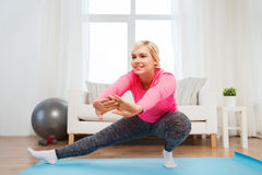 Donna felice che allunga gamba sulla stuoia a casa Fotografia Stock Libera da Diritti