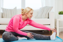Donna felice che allunga gamba sulla stuoia a casa Immagine Stock