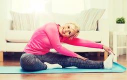 Donna felice che allunga gamba sulla stuoia a casa Immagini Stock