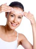 Donna felice che applica crema sulla sua fronte Fotografia Stock