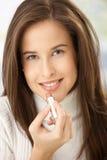 Donna felice che applica rossetto immagini stock
