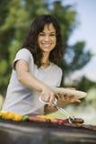 Donna felice che arrostisce col barbecue al parco Immagine Stock Libera da Diritti
