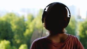 Donna felice che ascolta la musica e che guarda attraverso la finestra video d archivio