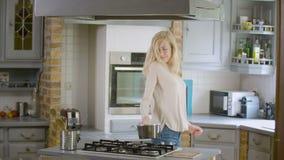 Donna felice che balla e che prepara un vaso sulla stufa per iniziare a cucinare video d archivio