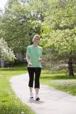 Donna felice che cammina con il giocatore MP3 Immagini Stock Libere da Diritti