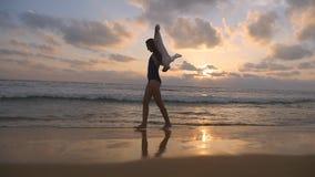 Donna felice che cammina e che fila sulla spiaggia vicino all'oceano Giovane bella ragazza che gode della vita e che si diverte i archivi video