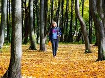 Donna felice che cammina nel parco di autunno Immagini Stock Libere da Diritti