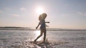 Donna felice che cammina sulla spiaggia dell'oceano e che spruzza l'acqua con i suoi piedi Giovane bella ragazza che gode della v Fotografia Stock Libera da Diritti
