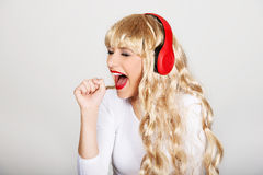 Donna felice che canta e che ascolta la musica Fotografia Stock