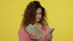 Donna felice che conta i contanti dei soldi su fondo giallo Denaro contante di conteggio della donna archivi video