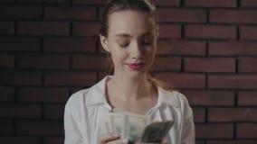 Donna felice che conta soldi dopo la conquista nella lotteria sul fondo del muro di mattoni video d archivio