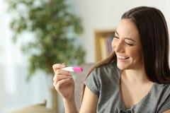 Donna felice che controlla test di gravidanza Fotografia Stock