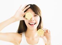 Donna felice che copre il suo occhio di limone immagini stock