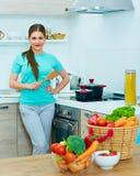 Donna felice che cucina alimento a casa immagini stock libere da diritti