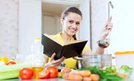 Donna felice che cucina con il libro a fotografia stock