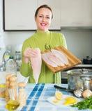 Donna felice che cucina la minestra del pesce Fotografia Stock