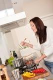 Donna felice che cucina la salsa di pomodori nella cucina fotografie stock libere da diritti