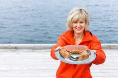 Donna felice che dà granchio cucinato sul piatto fotografie stock