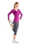 Donna felice che distoglie lo sguardo mentre allungando il muscolo della gamba Fotografia Stock