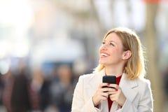 Donna felice che esamina il telefono della tenuta del lato nella via fotografia stock libera da diritti