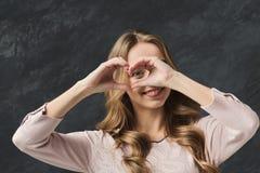 Donna felice che fa cuore con le sue dita Immagine Stock