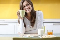 Donna felice che fa prima colazione fotografia stock