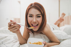 Donna felice che gode dei cereali dei fiocchi di granturco nella camera da letto immagini stock libere da diritti