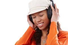 Donna felice che gode della musica tramite i trasduttori auricolari Fotografie Stock Libere da Diritti