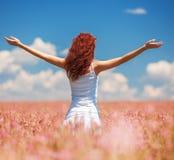 Donna felice che gode della vita nel campo con i fiori Fotografie Stock Libere da Diritti