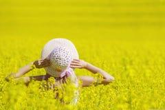 Donna felice che gode della vita nel campo con i fiori Bellezza della natura e campo variopinto con la violenza Stile di vita est Immagine Stock